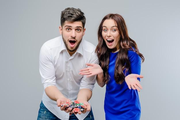 Attrayant couple jouant en ligne au casino avec des jetons de poker isolés sur fond gris