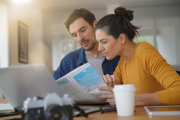 Attrayant couple qui planifie son voyage en regardant la carte à la maison