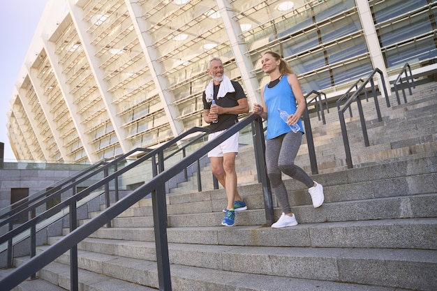 Attrayant couple sportif d'âge moyen homme et femme en vêtements de sport s'entraînant ensemble à l'extérieur