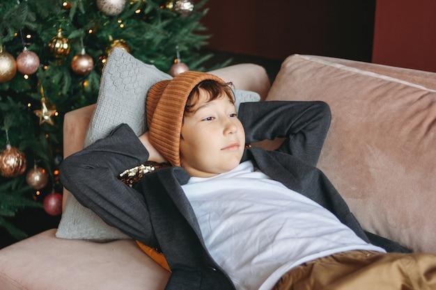 Attrayant drôle garçon tween aux cheveux noirs en chapeau en attente de nouvel an sur le canapé sur l'arbre de noël