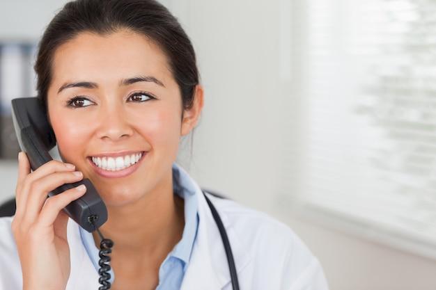 Attrayant femme médecin au téléphone et posant