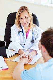 Attrayant femme médecin suspend la main de son patient masculin