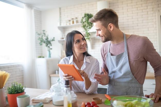 Attrayant femme souriante tenant une tablette orange pendant la cuisson avec son mari