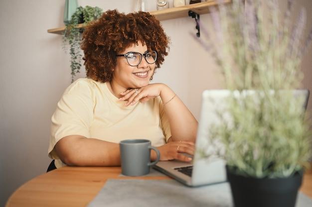Attrayant heureux élégant taille plus femme noire africaine étudiante cheveux afro dans des verres étudiant en ligne