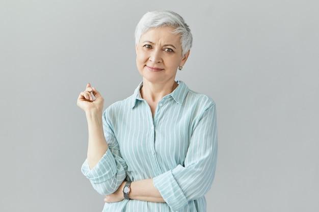 Attrayant positif femme européenne d'âge moyen en chemise rayée souriant en toute confiance avec le doigt avant soulevé posant isolé contre un mur blanc avec copyspace pour votre information