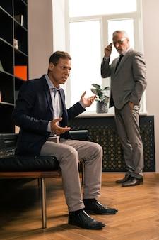 Attrayant psychothérapeute élégant portant des lunettes et un costume gris tout en regardant le comportement de son patient inquiet