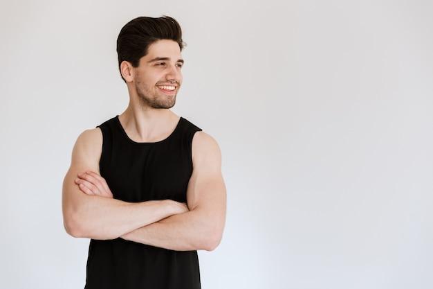 Attrayant souriant fit jeune sportif debout isolé sur mur blanc, bras croisés