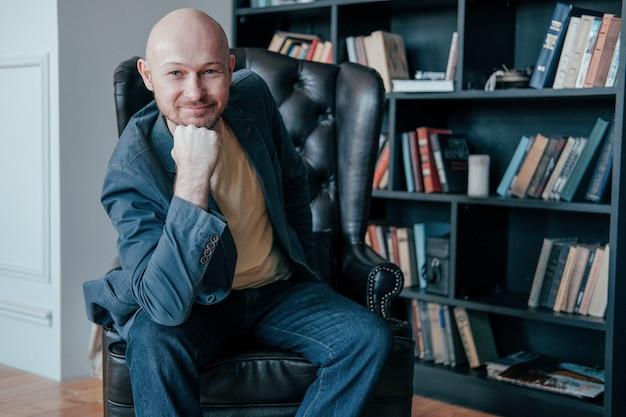 Attrayant succès adulte chauve souriant homme à la barbe en costume assis sur une chaise dans son bureau