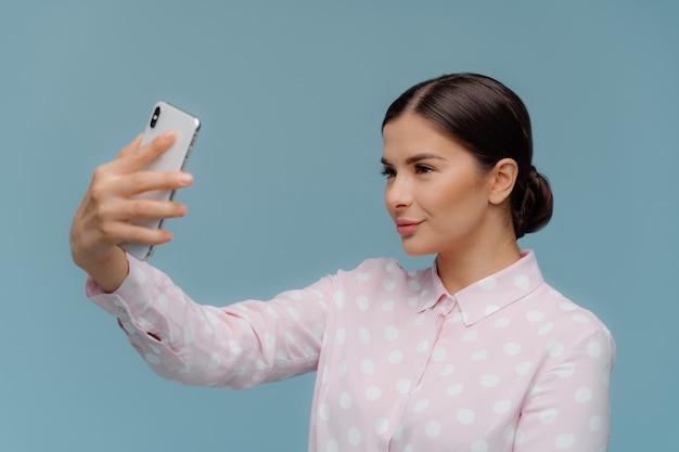 Attrayante enseignante élégante aux cheveux noirs faisant un portrait de selfie