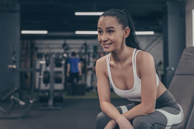 Attrayante sportive souriant gaiement, regardant au loin, se détendre à la salle de sport