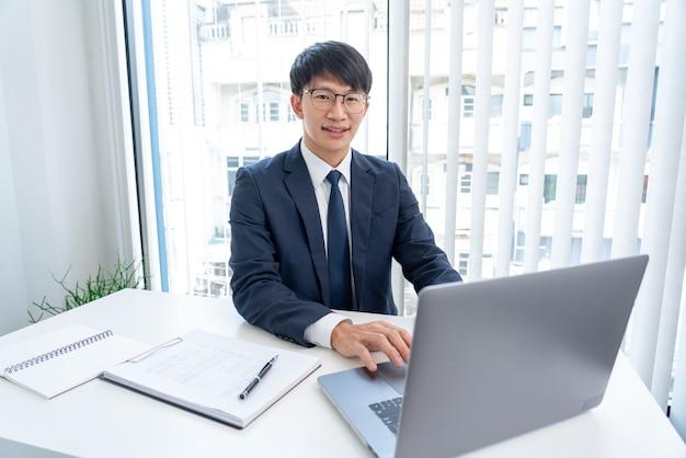 Attrayants beaux hommes d'affaires asiatiques dans des verres souriant heureux heureux