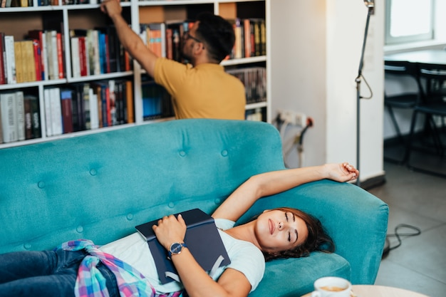 Attrayants jeunes étudiants fatigués homme et femme apprenant et se reposant dans la bibliothèque universitaire et apprenant.