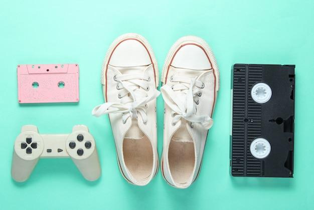 Attributs de la culture pop des années 80 sur fond de couleur menthe. baskets anciennes, manette de jeu, cassette audio, bande vidéo. minimalisme, vue de dessus