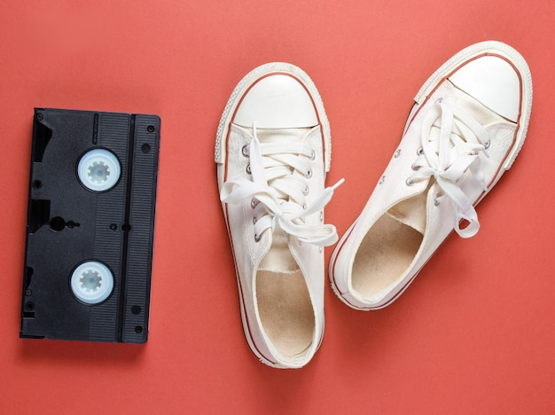 Attributs de la culture pop avec des baskets blanches rétro et une bande vidéo