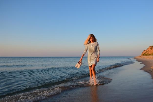 Au bord de la mer contre un ciel bleu, une fille blonde marche sur l'eau tenant des chaussures à la main
