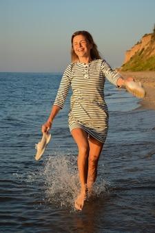 Au bord de la mer sur fond de ciel, une fille blonde court sur l'eau, sourit et tient des chaussures à la main