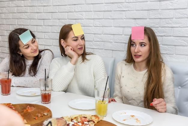Au café, des amis mangent de la pizza, discutent et jouent à des jeux