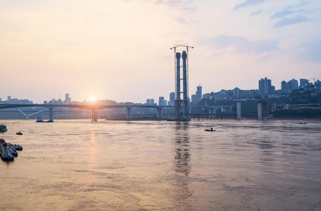 Au coucher du soleil, le pont sur le fleuve yangtsé en construction à chongqing, en chine