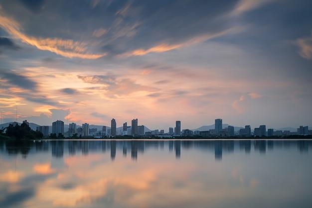 Au crépuscule, le lac reflète la vue nocturne de la ville