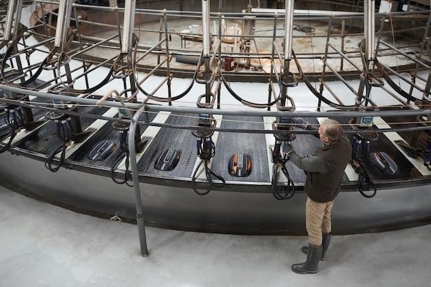 Au-dessus de l'arrière-plan de l'ouvrier mature mise en place de machine à traire industrielle vache à la ferme laitière moderne, espace copie