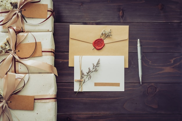 Au-dessus d'une boîte-cadeau artisanale et d'une carte de voeux avec un stylo sur fond de table en bois