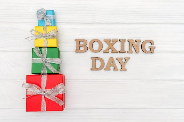 Au-dessus des coffrets cadeaux est attaché avec un ruban avec des mots boxing day sur bois blanc