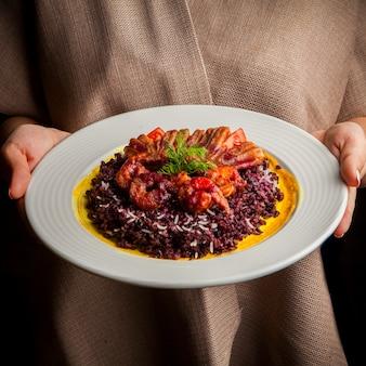 Au-dessus des crevettes dans la pâte avec du riz rouge et des verts et la main de l'homme dans une assiette blanche