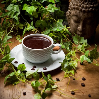 Au-dessus du café turc avec des grains de café et une branche de raisin et une tête de statue dans une tasse