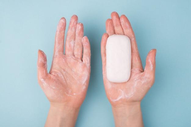 Au-dessus du haut, vue rapprochée, photo de mains utilisant une barre de savon et du savon crémeux isolés sur une surface de couleur bleue