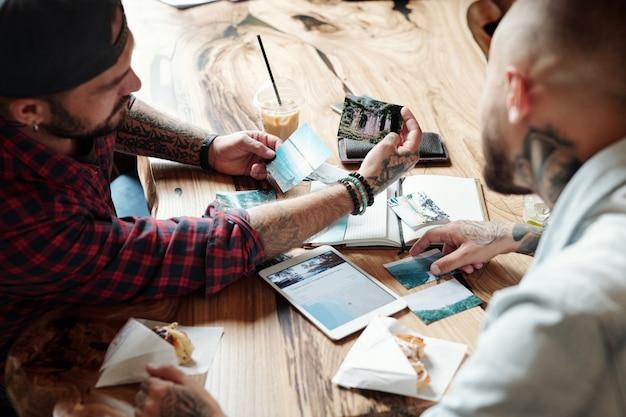 Au-dessus de l'épaule de l'homme moderne montrant des photographies de voyage à un ami alors qu'ils se rassemblent au café