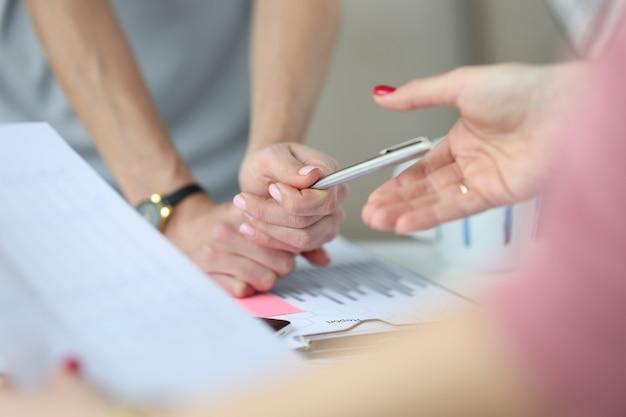 Au-dessus des mains de la table de travail et d'un stylo sur la table se trouvent des graphiques avec le développement commercial des chiffres d'affaires
