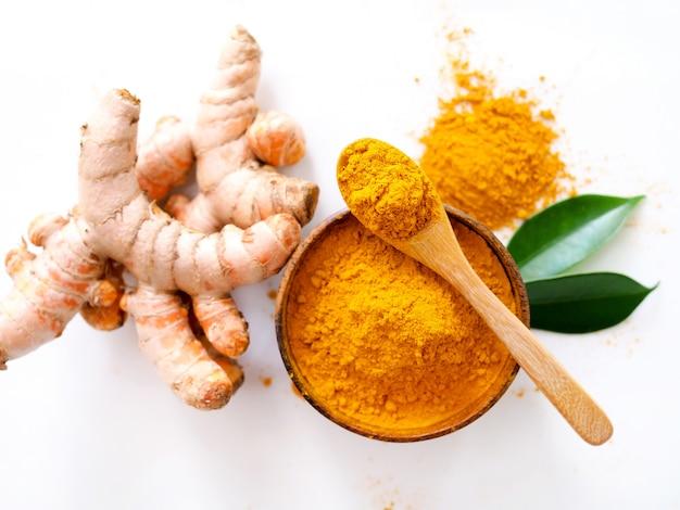 Au-dessus de poudre de curcuma dans un bol en bois et racine de curcuma, légumes à base d'herbes pour la peau ou la cuisson isolé sur une surface blanche.