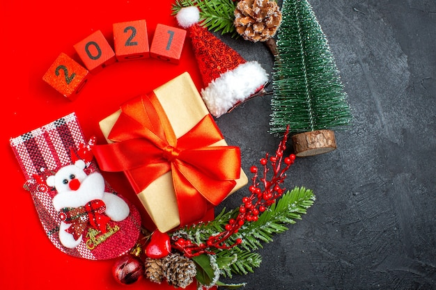 Au-dessus de la vue de beaux accessoires de décoration cadeau branches de sapin numéros de chaussette de noël sur une serviette rouge et arbre de noël chapeau de père noël sur fond sombre