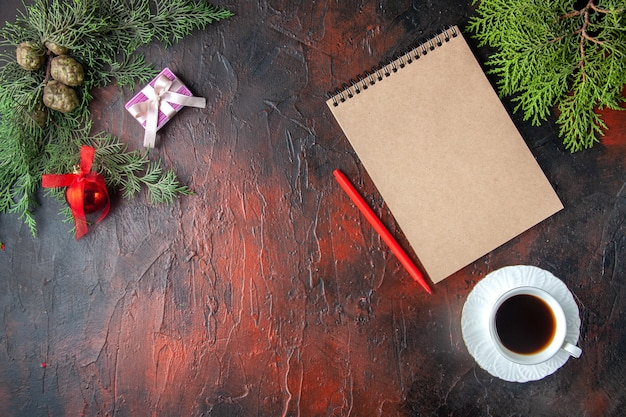 Au-dessus de la vue des branches de sapin, une tasse d'accessoires de décoration de thé noir et un cadeau à côté d'un cahier avec un stylo sur fond sombre