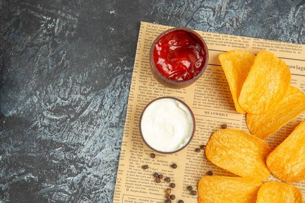 Au-dessus de la vue de délicieux chips maison et ketchup mayonnaise bol de poivre sur papier journal sur tableau gris