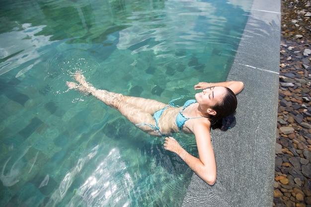 Au-dessus de la vue de la femme heureuse appréciant le repos dans la piscine