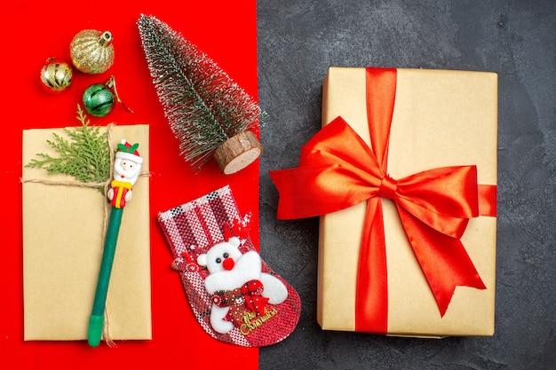 Au-dessus de la vue de l'humeur de noël avec des accessoires de décoration d'arbre de noël chaussette cadeau sur fond rouge et noir