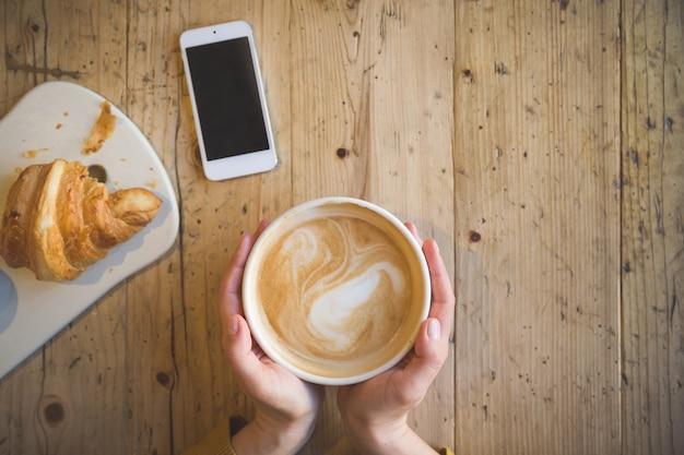 Au-dessus de la vue des mains féminines tenant une tasse de café chaud et avec un téléphone intelligent avec sur une table en bois