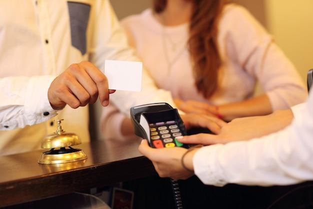 Au milieu du couple au comptoir payant pour l'hôtel