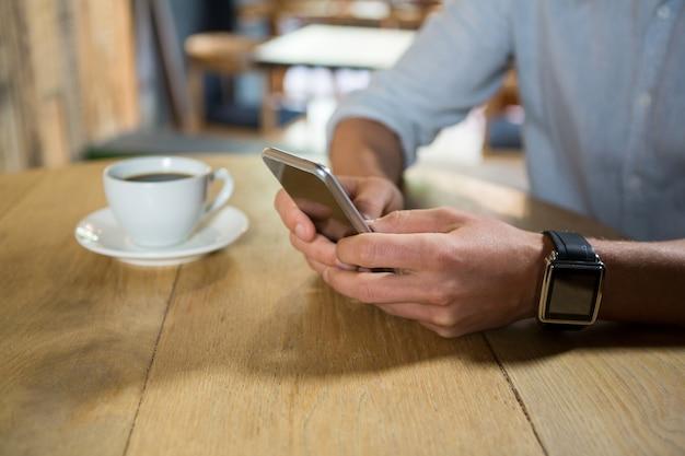 Au milieu du jeune homme à l'aide de téléphone portable à table dans un café