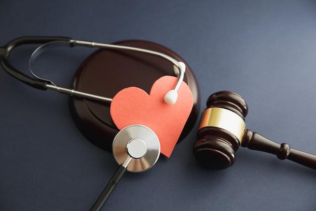 Au milieu du juge frappant maillet avec stéthoscope au bureau dans la salle d'audience