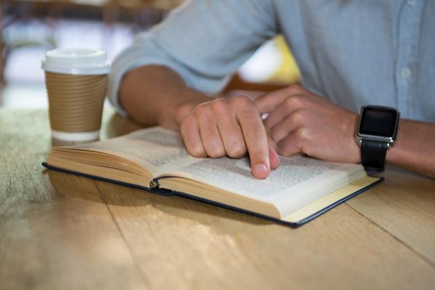 Au milieu du livre de lecture de jeune homme à table dans un café