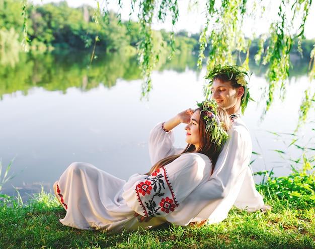 Au milieu de l'été. jeune couple d'amoureux en costumes slaves sur la rive du lac. fête slave d'ivan kupala.