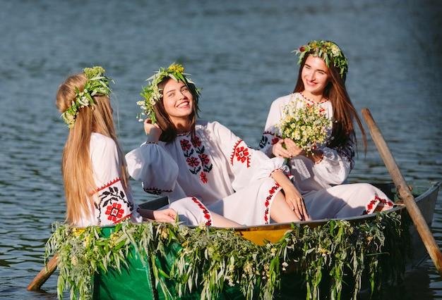 Au milieu de l'été. des jeunes filles en costumes nationaux naviguent dans un bateau décoré de feuilles et de croissances. fête slave d'ivan kupala.