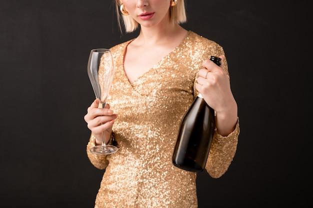Au milieu de la jeune femme assez élégante tenant un verre à vin et une bouteille de champagne tout en allant l'avoir à l'anniversaire ou à la fête du nouvel an