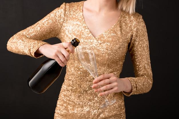 Au milieu de la jeune femme élégante versant du champagne à partir de la bouteille dans le verre à vin tout en allant l'avoir à l'anniversaire ou à la fête du nouvel an