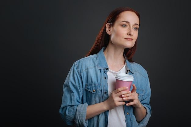 Au plaisir de vous rencontrer. superbe belle femme concentrée tenant une tasse de café dans ses mains et cherchant son amie dans une foule pendant qu'ils planifient une réunion maintenant