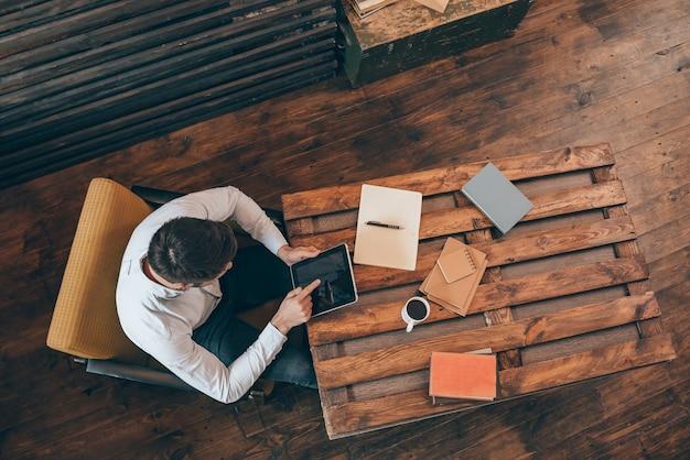 Au plus profond de son travail. vue de dessus du jeune homme travaillant sur le pavé tactile alors qu'il était assis sur son lieu de travail