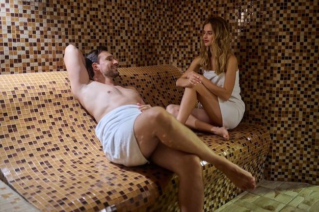 Au sauna. un couple passe du temps ensemble dans un sauna et a l'air détendu