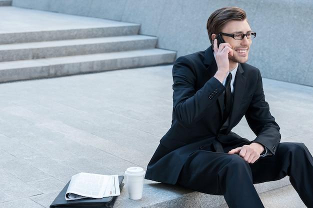 Au téléphone. homme d'affaires réussi parlant avec le téléphone portable tout en s'asseyant sur des escaliers